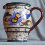 Dartmouth Pottery jug with orange peel type surface and unusual decoration